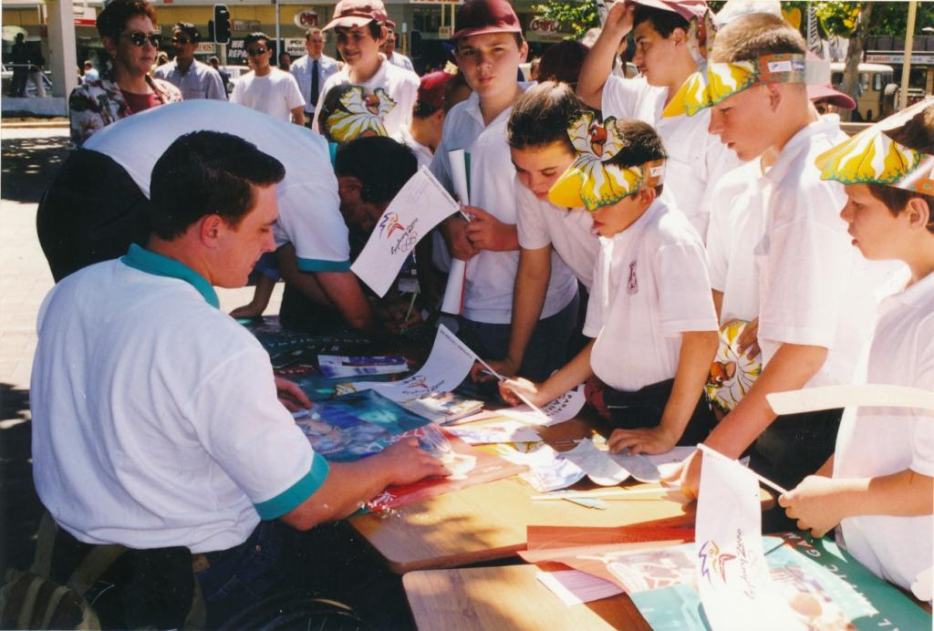PRS118_091_001: Athlete signing autographs at Paralympic Expo in Church Street Mall, Parramatta, 1997 (City of Parramatta Council Archives)